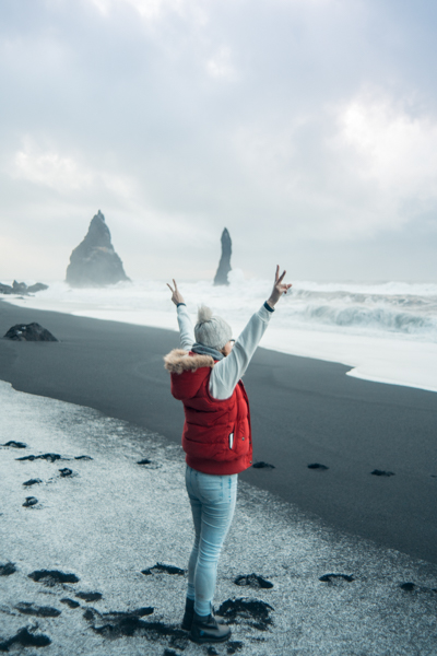 Girl standing on Reynisfjara Black Sand Beach in Iceland
