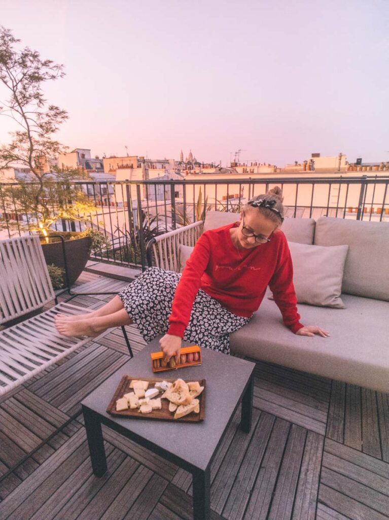 Girl eating macarons and cheeseboard on rooftop of Paris hotel