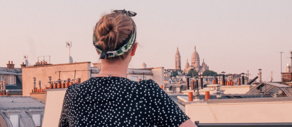 Back of woman's head looking out to Sacre Coeur in Paris