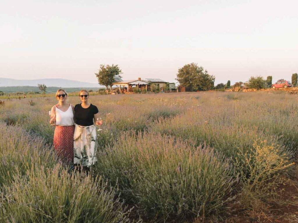 Two girls standing in lavender fields at Hora Farm, on Croatia's Hvar Island