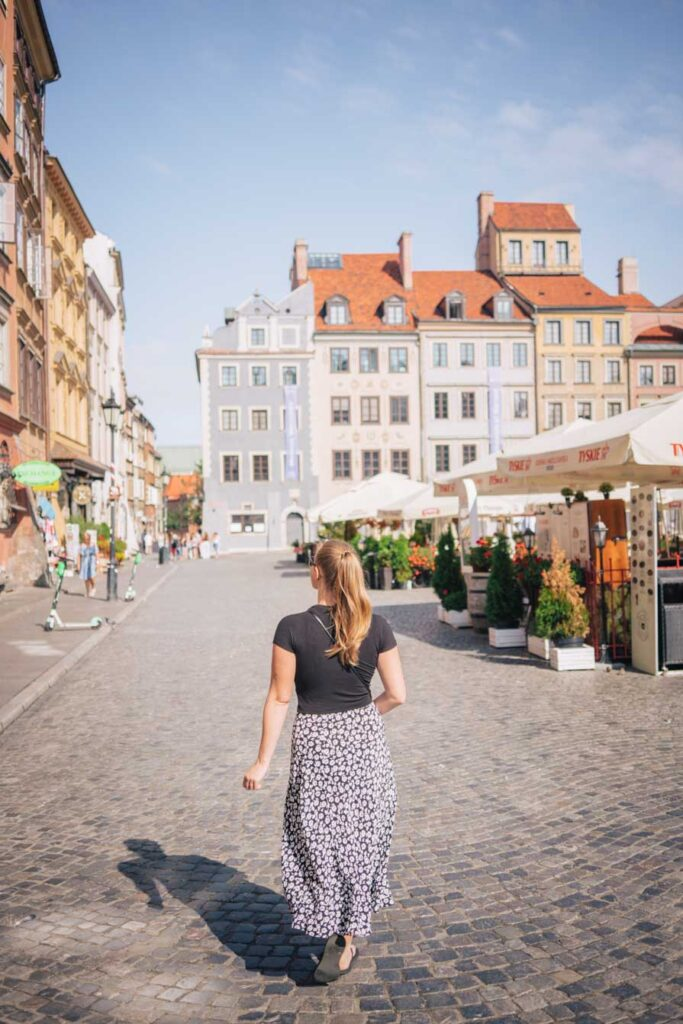 Girl walking in front of colourful houses in Warsaw Old Town