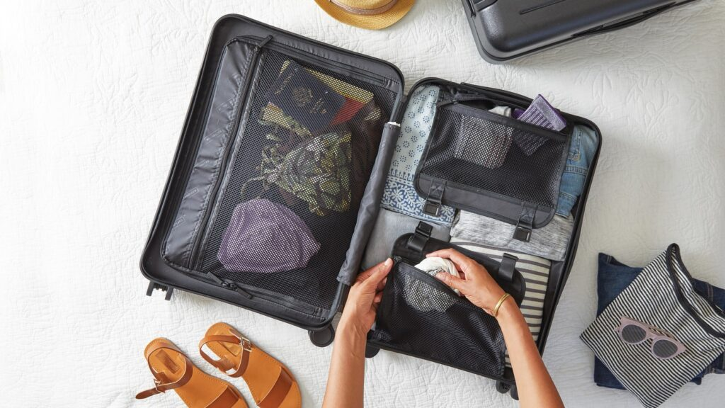 Girl packing suitcase with clothes