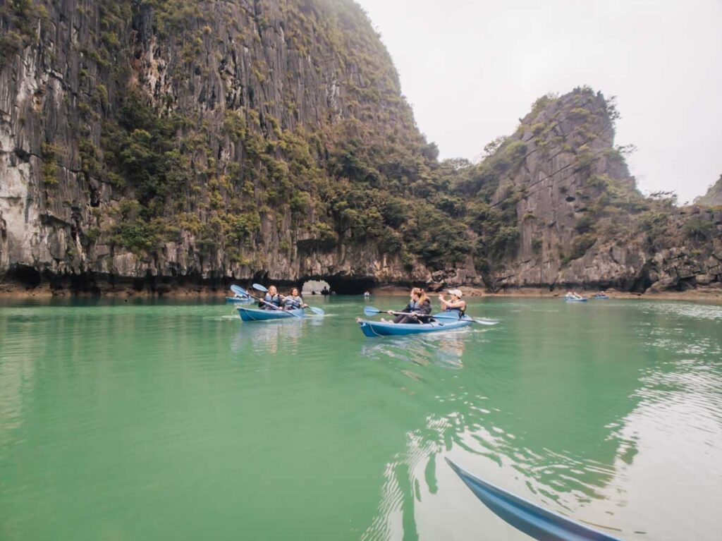 Kayaking at Halong Bay in front of limestone karsts