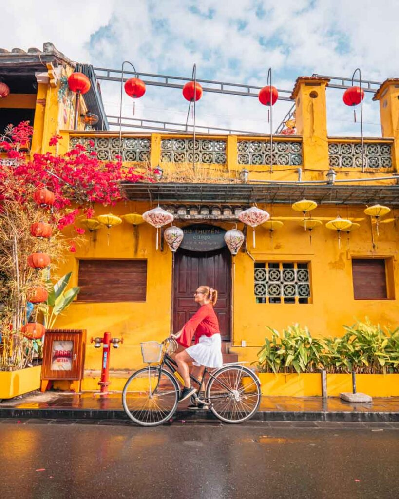 Girl riding bike in front of store and lanterns in Hoi An