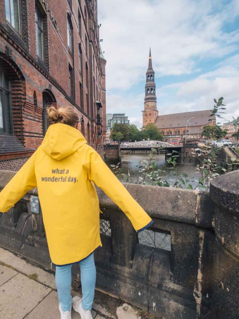 Girl in rainjacket that says 'what a wonderful day' in front of Hamburg Harbour