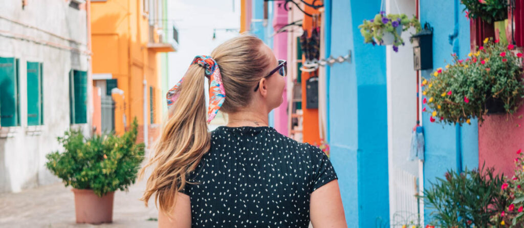 Girl with ponytail walking in front of colourful houses in Burano