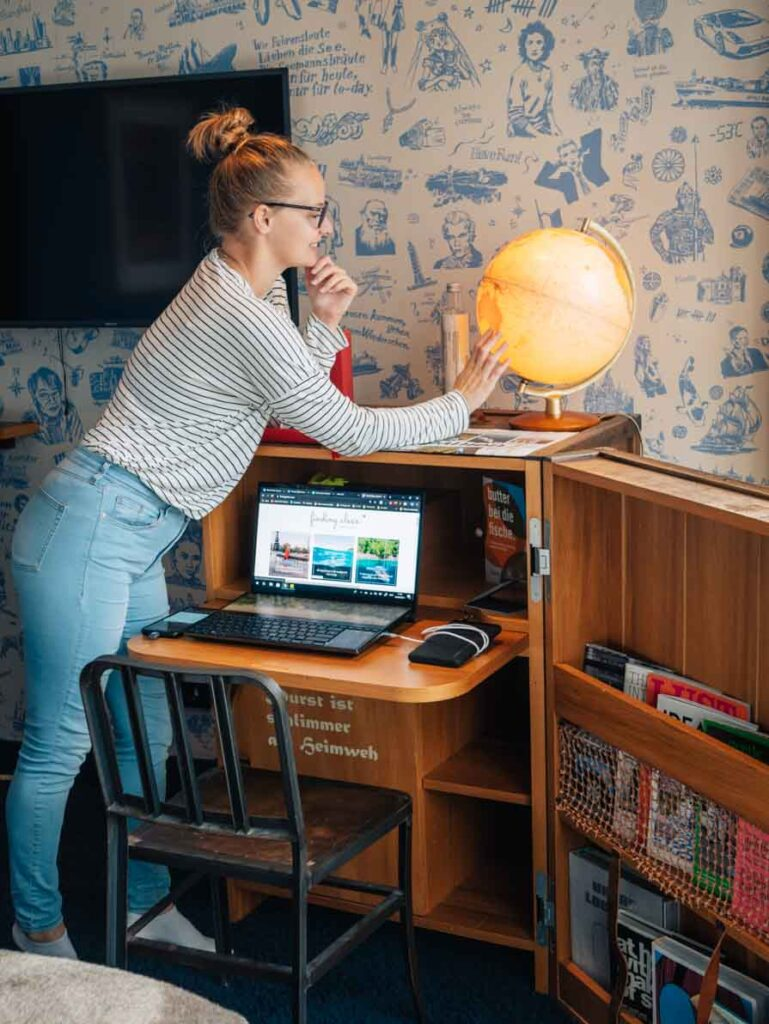Girl looking at globe on desk with laptop at hotel in Hamburg