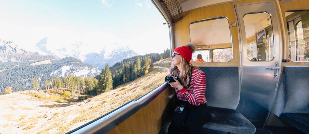 Girl sitting on train looking out at mountains in Swiss Alps