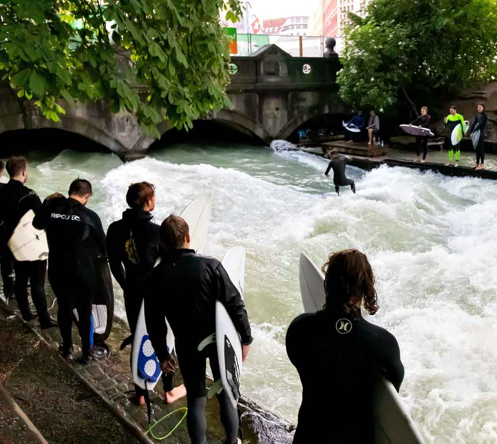 Surfers catching a wave at the Munich Eisbach surf spot
