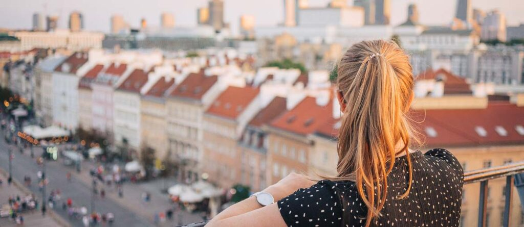 Girl looking at colourful houses from viewpoint in Warsaw