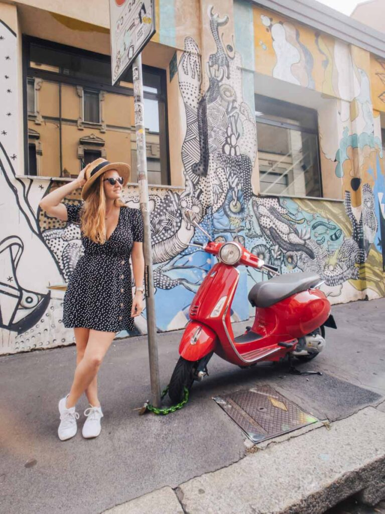 Girl and vespa in front of street art in Milan Isola