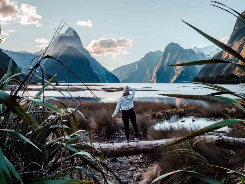 girls standing on log in front of milford sound sunset