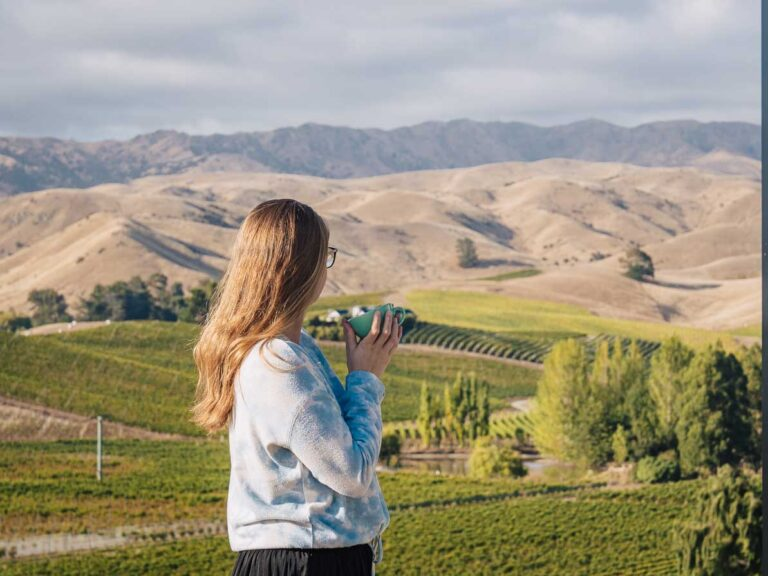 girl holding coffee cup in front of vineyard in blenheim