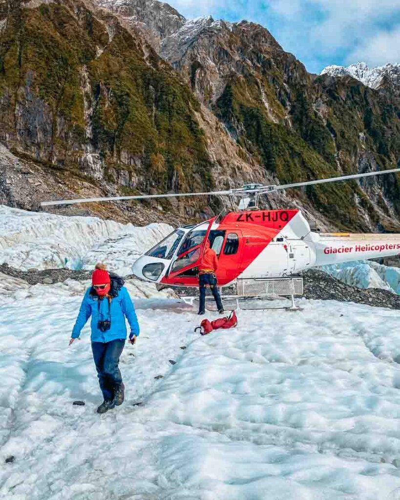 girl walking out of helicopter on franz josef glacier