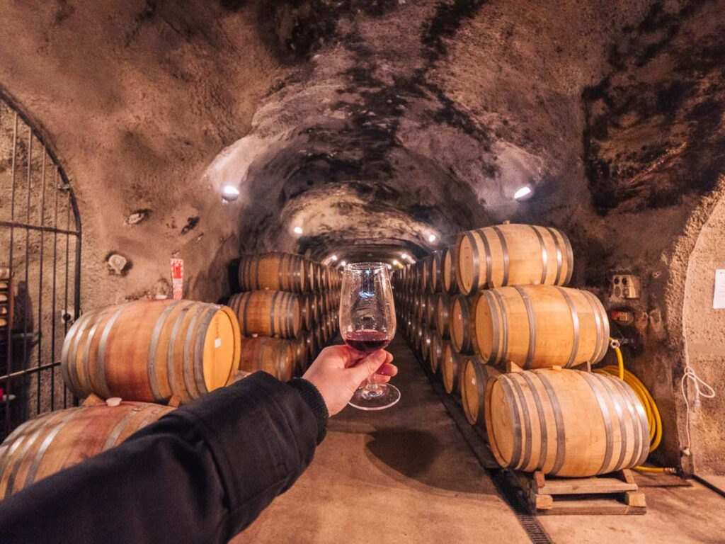 wine glass in front of barrels in wine cave at gibbston valley